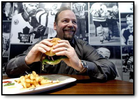 Photo of Wendel enjoying a burger and fries.